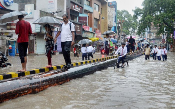 Varanasi: Pedestrians walk through a waterlogged road following heavy rainfall, in Varanasi. (PTI Photo)