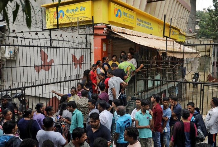 People wait outside a PMC (Punjab and Maharashtra Co-operative) Bank branch to withdraw their money in Mumbai. (PTI Photo)