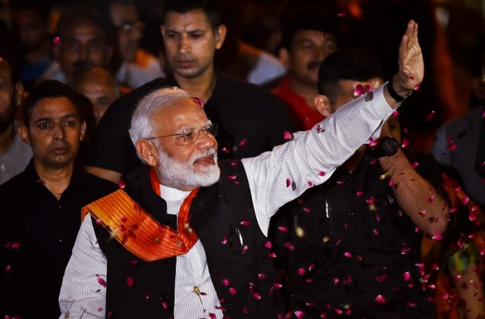 Prime Minister Narendra Modi waves at BJP supporters as he is accorded a grand welcome on his arrival after the week-long US visit. (PTI Photo)
