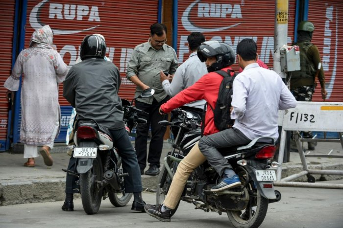 Security personnel stop commuters on motorcycles as they stand guard to block a road while strict restrictions are imposed during a lockdown in Srinagar. (AFP Photo)