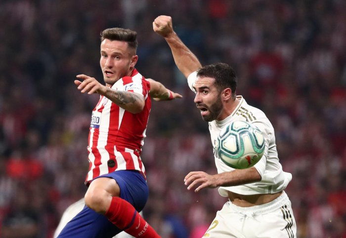Real Madrid's Dani Carvajal in action with Atletico Madrid's Saul Niguez. Photo/REUTERS