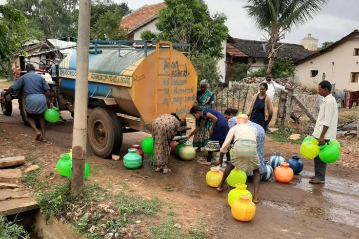 People collect water from tanker at Hosahalli in Kadur taluk.