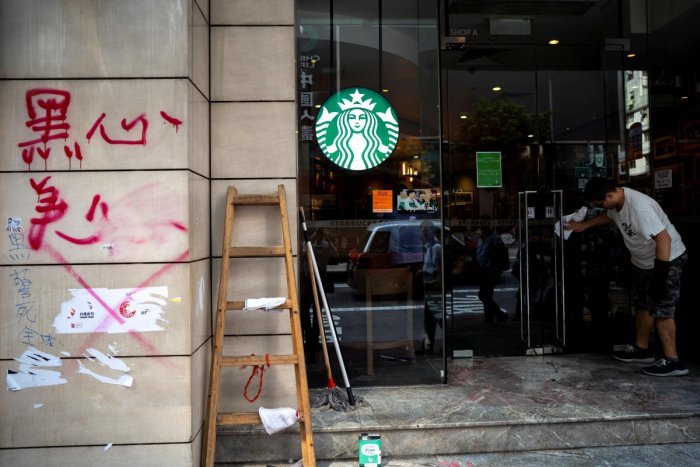 A worker cleans graffiti sprayed by anti-government protesters at a Starbucks coffee shop a day after a protest in Causeway Bay district, Hong Kong, China, September 30, 2019. (REUTERS)