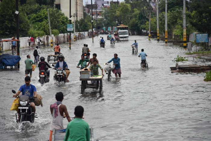 Commuters make their way on a waterlogged road following heavy rainfalls in Patna. (PTI Photo)