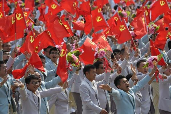 People wave Communist Party flags during a military parade in Tiananmen Square in Beijing. (Photo/AFP)