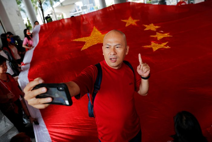Pro-China supporter Alex Yeung, owner of Wah Kee Restaurant, reacts next to a giant Chinese national flag as he and others celebrate China's National Day in Hong Kong, China October 1, 2019. Reuters