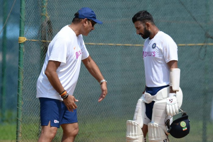 India's Head Coach Ravi Shastri (left) demonstrates a finer pointto Cheteshwar Pujara during a practice session in Visakhapatnam on Tuesday.AFP
