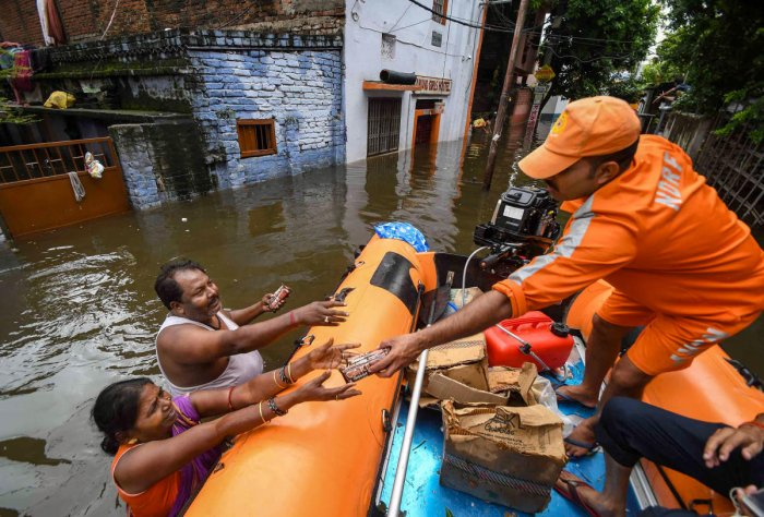 National Disaster Response Force (NDRF) workers distribute relife material to flood-affected people of Rajendra Nagar area after heavy rains, in Patna, Tuesday, Oct. 01, 2019. (PTI Photo)