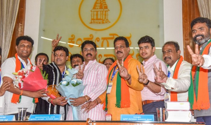 R Ashok greets C R Ramamohan Raju new deputy Mayor, M Gautham Kumar, new Mayor after BBMP Mayor and Deputy election at Kempegowda Council Hall, Bengaluru on Tuesday. S R Vishwanath, Tejasvi Suraya and others seen.
