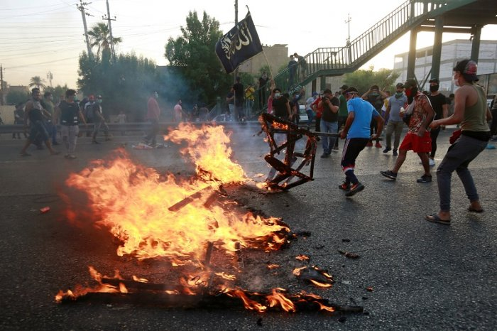Demonstrators burn objects at a protest during a curfew, two days after the nationwide anti-government protests turned violent, in Baghdad, Iraq. (Reuters Photo)