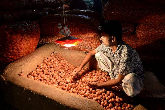 A salesman prepares onions at Kawran Bazaar wholesale market in Dhaka. (AFP Photo)