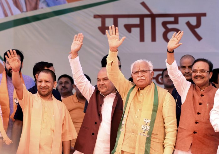 Haryana Chief Minister (2nd R) along with Union minister and senior BJP leader Narendra Singh Tomar, UP CM Yogi Adityanath and party leader Anil Jain waves at supporters during a rally before filing his nomination papers, in Karnal. (PTI Photo)