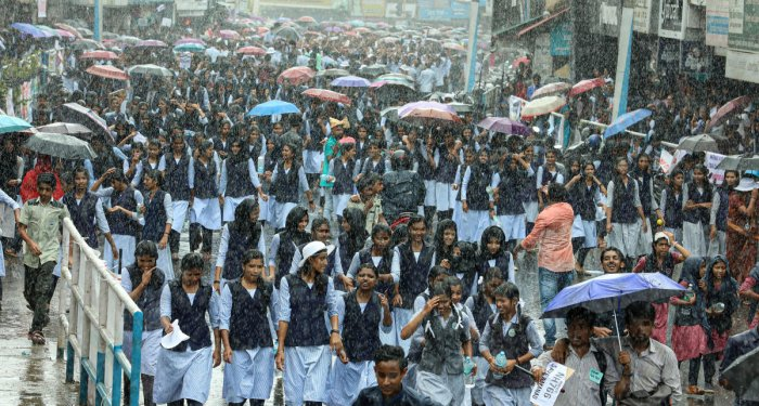 School students take part in a protest march amid rains against the night traffic ban on Kozhikode-Bengaluru National Highway (NH 766), at Sultan Bathery in Wayanad on Oct 1, 2019. (PTI Photo)