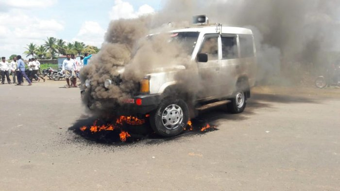 A group of locals set a police vehicle on fire following the collision between a tomtom and a government bus at Kolhar in Vijayapura district on Wednesday. DH PHOTO