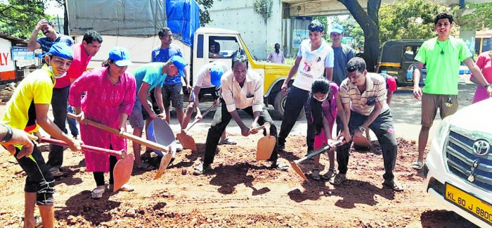 Youth engage in repairing the road by filling potholes at Kulshekar in Mangaluru on the occasion of Gandhi Jayanti on Wednesday.