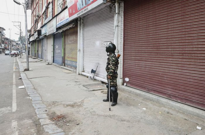 A security person stands guard during shutdown, in Srinagar on Thursday. (PTI Photo)