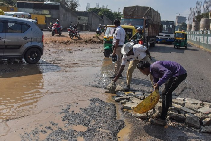 Mico lay out Traffic police filling road holes by the help of local workers, at Bannerghatta Road in Bengaluru.