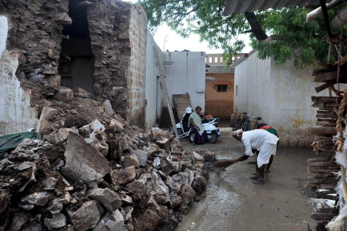 Residents of Kamatagi village in Bagalkot cleans the slush following floods in the village damaging several houses in the area. | DH Photo: Pushkar V
