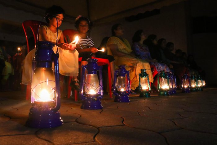 Residents of Holy Faith H2o at Maradu, one of the flats built on the coastal zone, light lamps and candles after the decison of Supreme Court on Rs 25 lakh interim compensation to each flat owner, in Kochi. (PTI Photo)