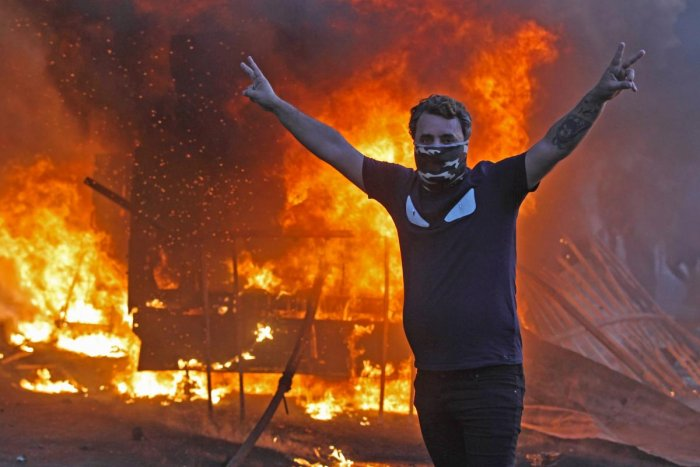 A protester flashes the V for victory sign as a riot police vehicle burns behind him during clashes amidst demonstrations against state corruption, failing public services, and unemployment in the Iraqi capital Baghdad's central Tayeran Square on October
