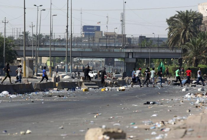 Iraqi protesters gather amidst garbage and debris on October 4, 2019 during demonstrations against state corruption, failing public services, and unemployment in the Iraqi capital Baghdad's central Khellani Square. AFP