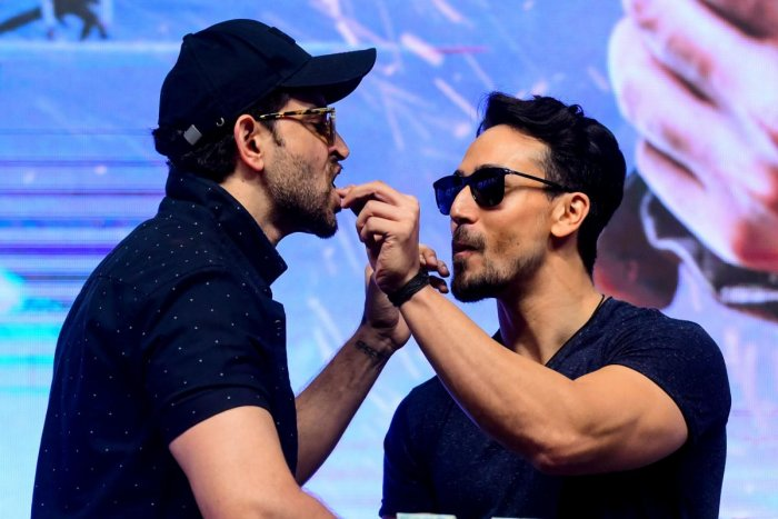 Bollywood actors Hrithik Roshan (L) and Tiger Shroff (R) interact with eachother during the promotion of their action thriller Hindi film 'War' in Mumbai on October 4, 2019. (AFP)