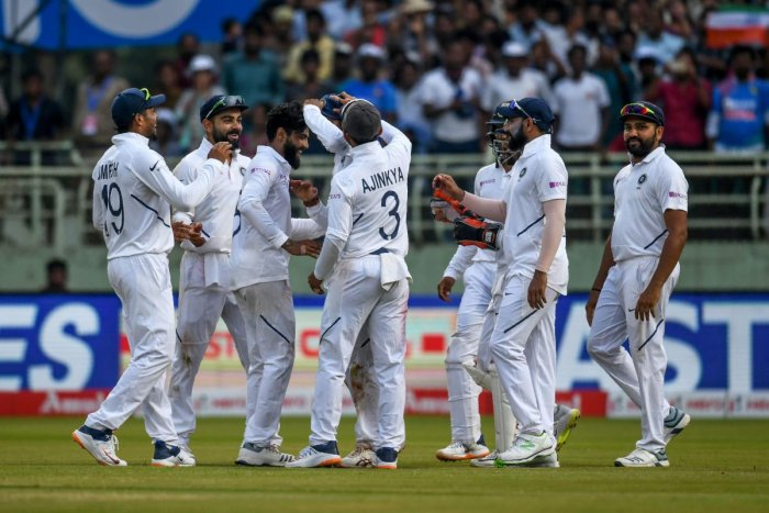 Ravindra Jadeja (3L) celebrates with teammates after the dismissal of South Africa's Dean Elgar during the third day's play of the first Test match between India and South Africa at the Dr. Y.S. Rajasekhara Reddy ACA-VDCA Cricket Stadium in Visakhapatnam
