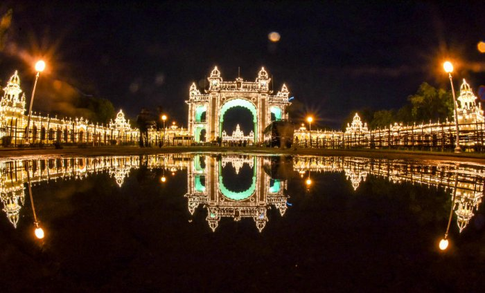 Reflection of the Mysuru Palace, from Jayamarthanda Gate, on the Exhibition Grounds side, all decked up for the Dasara celebration, in Mysuru, on Tuesday. It rained for some time on Tuesday evening. (DH Photo/B R Savitha)