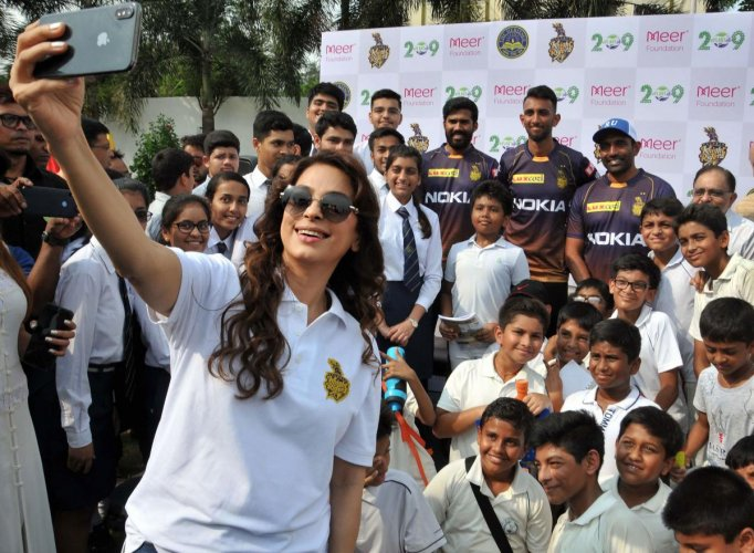 Bollywood actor and Kolkata Knight Riders co-owner Juhi Chawla takes selfie with school students and KKR team players Robin Uthappa, Sandeep Warrier and Prasidh Krishna during a promotional event, in Kolkata, Thursday, Oct. 3, 2019. (PTI Photo)