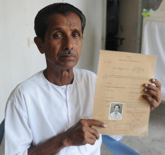 Nirepada Mallick (74) shows his citizenship certificate in RH-2 camp in Sindhanur. DH Photo/Pushkar V