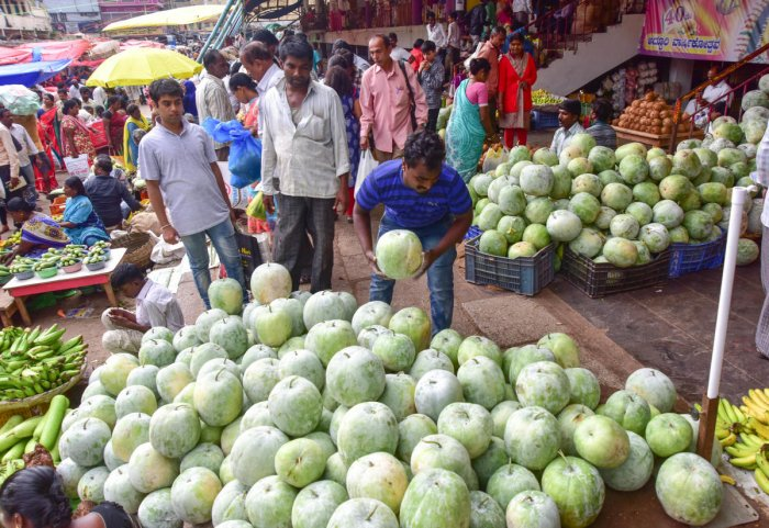 People purchase ash gourd and banana stems ahead of Ayudha Pooja and Vijayadashami festivals at KR market on Friday. The festivals are celebrated on Monday and Tuesday. DH PHOTOs/IRSHAD MAHAMMAD