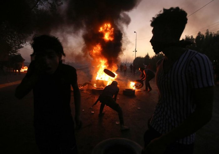 Iraqi protesters burn tyres during a demonstration against state corruption, failing public services, and unemployment, in the Iraqi capital Baghdad. (AFP Photo)