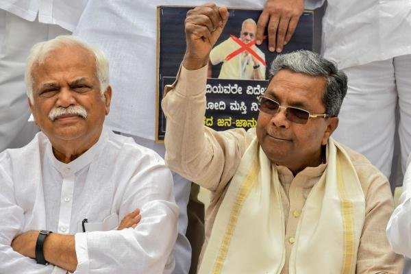 Senior Congress leader and former Chief Minister of Karnataka, Siddaramaiah (R), along with Congress legislators and leaders stage a demonstration at the Gandhi statue in Vidhana Soudha in Bangalore on September 18, 2019, against Bharatiya Janata Party (BJP) government for the delay in providing relief to the flood victims. (Photo / AFP)
