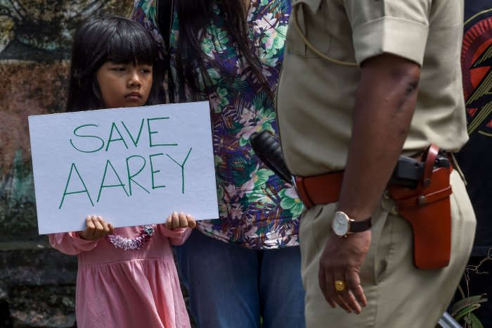 "A policeman walks past a child holding a poster as she protests against the destruction of Aarey forest which they call ""Mumbai's Amazon"", after the government approved cutting down 2,700 trees for constructing a metro train car shed, in Mumbai. (AFP Photo)"