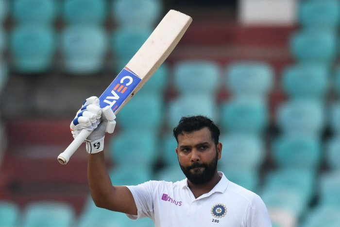 Indian cricketer Rohit Sharma raises his bat after scoring 100 runs during the fourth day's play of the first Test match between India and South Africa at the Dr. Y.S. Rajasekhara Reddy ACA-VDCA Cricket Stadium in Visakhapatnam on October 5, 2019. (AFP)