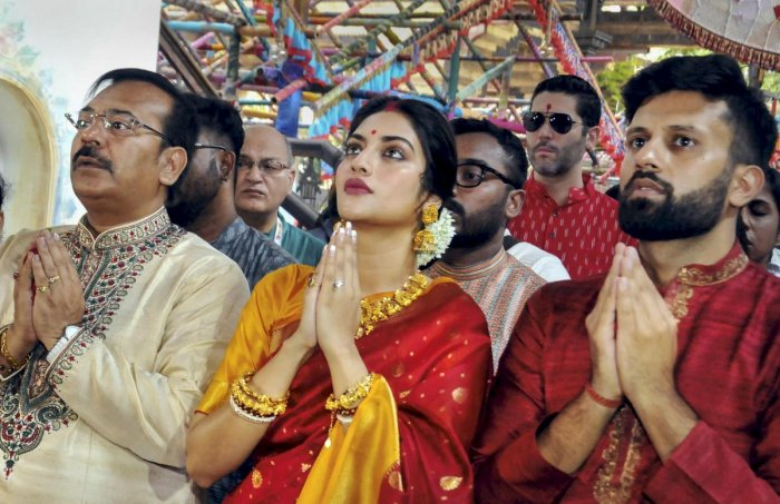 Noted film actress and Trinamool Congress MP Nusrat Jahan and her husband Nikhil Jain(R) participate in 'Pushpanjali' offering rituals of 'Maha Ashtami' during the ongoing Durga Puja festival, in Kolkata onSunday. West Bengal Minister Arup Biswas is also seen. (PTI Photo)
