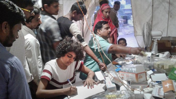 Doctors connected with an NGO provide medicines to flood-affected people at a makeshift OPD facility, in Patna, Saturday, Oct. 5, 2019. (PTI Photo)