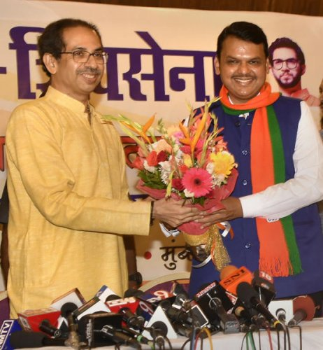 Maharashtra Chief Minister Devendra Fadnavis exchanges bouquets with Shiv Sena Chief Uddhav Thackeray during a press conference to announce Maha Yuti (Grand alliance), in Mumbai. (PTI photo)