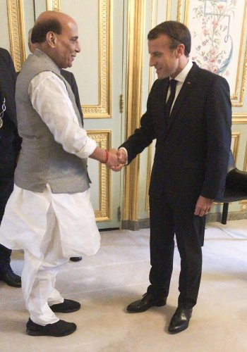Union Defence Minister Rajnath Singh shakes hands with French President Emmanuel Macron. (PTI Photo)
