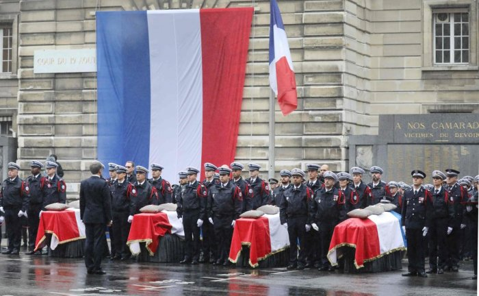 French President Emmanuel Macron stands in front of coffins during a ceremony at The Prefecture de Police de Paris (Paris Police Headquarters) in Paris on October 8, 2019, held to pay respects to the victims of an attack at the prefecture on October 4, 2019. AFP