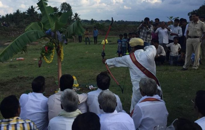 The head of Patela community, A M Mahesh, hitting an arrow at a bunch of bananas to mark Vijayadashami celebrations at Aradavalli in Chikkamagaluru taluk on Tuesday.