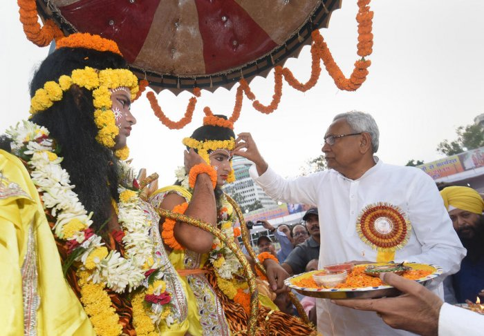 Bihar Chief Minister Nitish Kumar applies 'tilak' on the forehead of an artist dressed as Lord Ram during Dussehra celebrations at Gandhi Maidan in Patna, Tuesday, Oct. 8, 2019. Photo/PTI