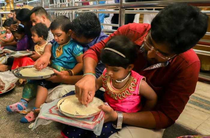 Parents initiate their children into world of learning and writing on the occasion of Vijayadashami. (PTI Photo)
