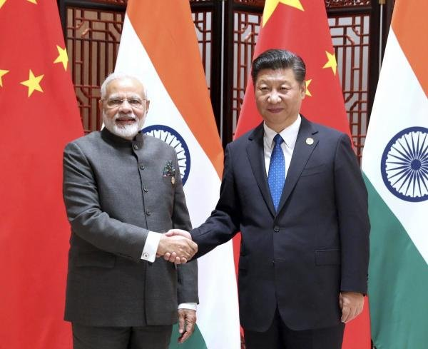In this photo released by China's Xinhua News Agency, Indian Prime Minister Narendra Modi, left, and China's President Xi Jinping shake hands as they pose for a photo during a meeting on the sidelines of the BRICS Summit in Xiamen in southeastern China's Fujian Province. (AP photo)