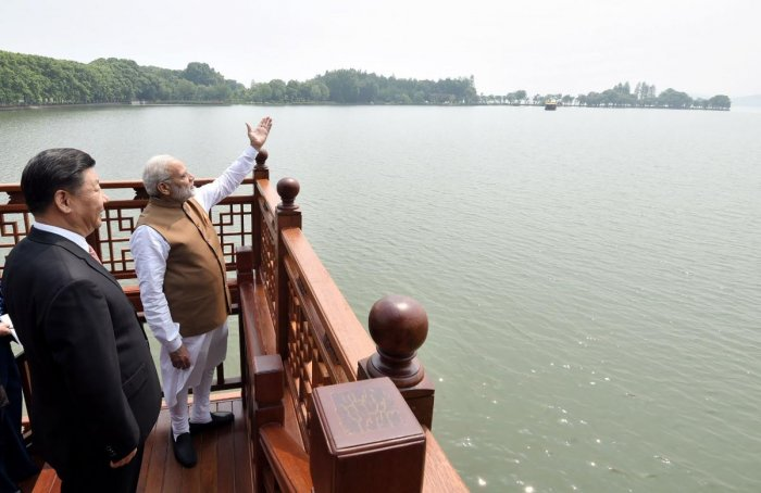Prime Minister Narendra Modi (R) and Chinese President Xi Jinping looking on in a house boat, at East Lake, in Wuhan. (Photo by Reuters)