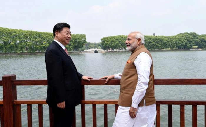 Chinese President Xi Jinping and India's Prime Minister Narendra Modi speak as they walk along the East Lake in Wuhan, China. (Photo by Reuters)