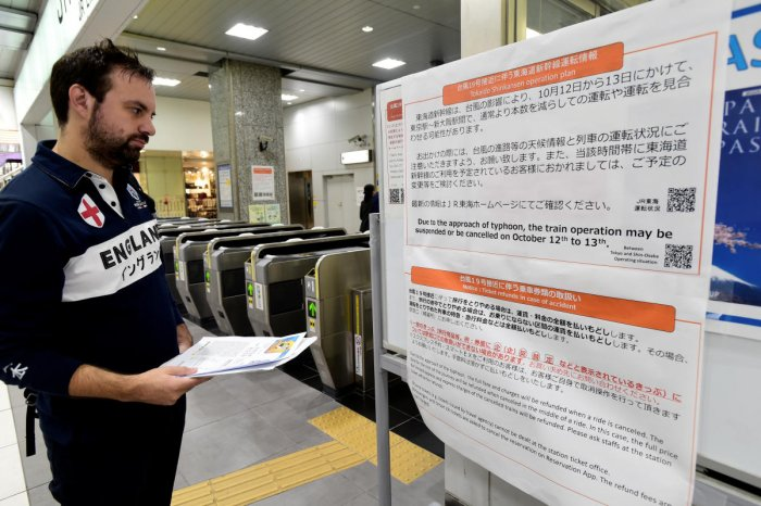 An England rugby supporter reads a travel warning sign at Hamamatsu railway station, regarding Typhoon Hagibis and possible train suspensions and cancellations in Hamamatsu, Japan, October 10, 2019. Reuters