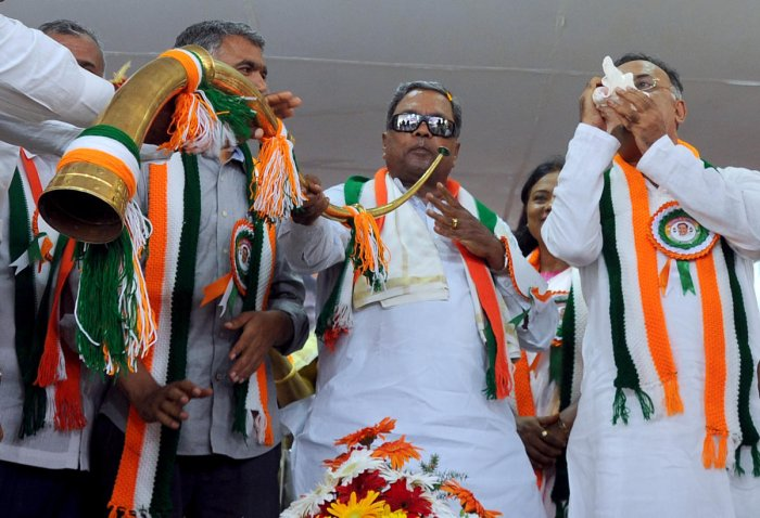 Former Chief Minister and senior Congress leader Siddaramaiah blows the poll bugle as KPCC President Dinesh Gundu Rao conch shell as former minister Krishna Byre Gowda and various party leaders take part in a public rally at Hosakote on Saturday. | DH Pho