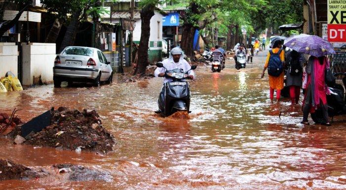 Water overflows on Laxmigudi Road at Vidyanagar following heavy rain in Hubballi on Thursday. DH photo