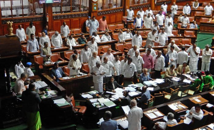 Members of the Opposition stage a protest, demanding a discussion on the state's flood situation, in the Assembly on Thursday.